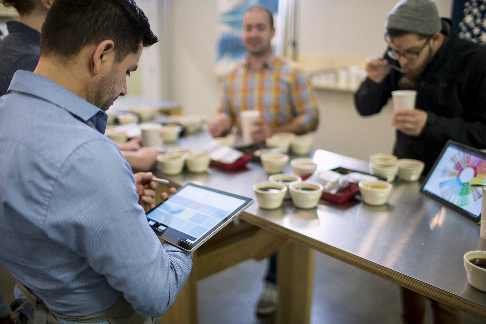 Customers tasting coffee while employee collects data from them