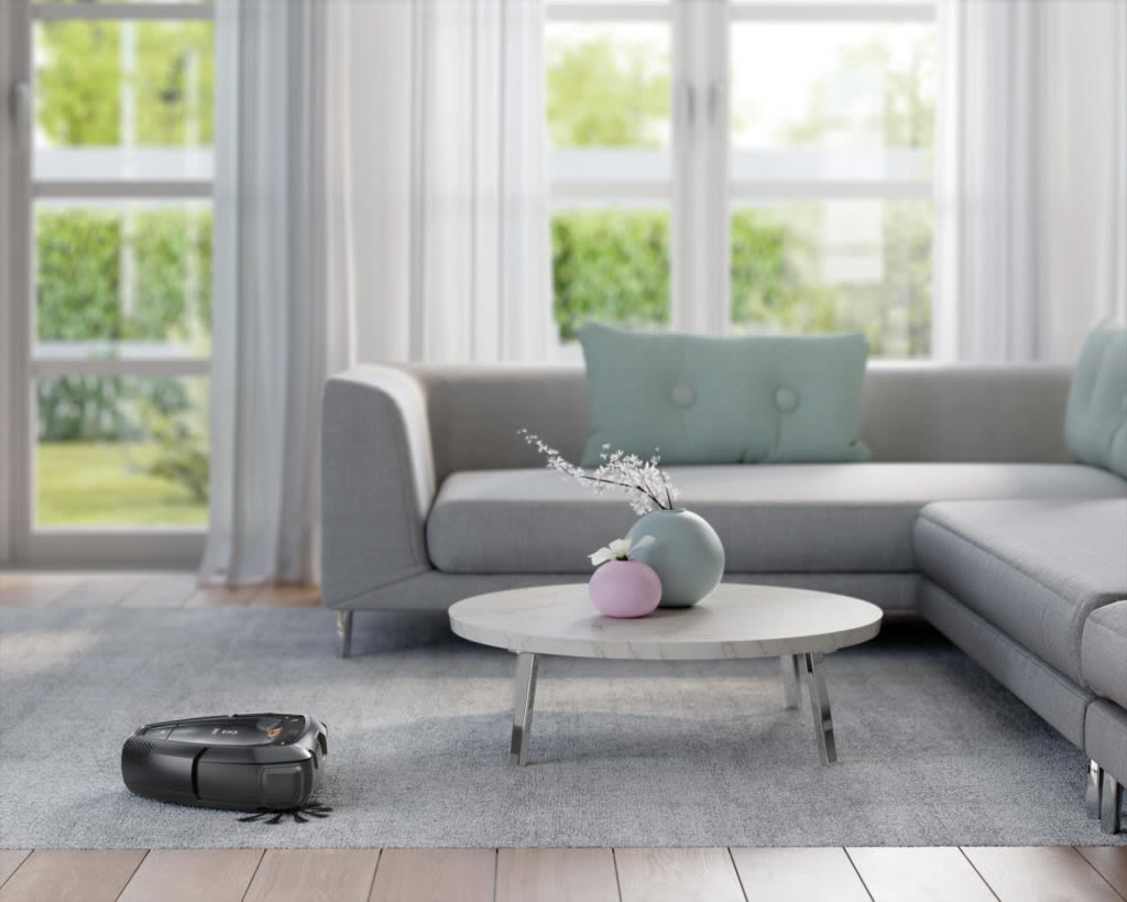 A Pure i9, a cloud-connected robot vacuum. cleans a rug and flooring while navigating a table and sofa