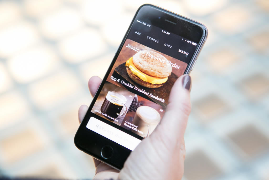 A smart phone displays personalized recommendations to customers via a mobile app