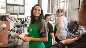 A Starbucks partner smiles at a customer while preparing coffee