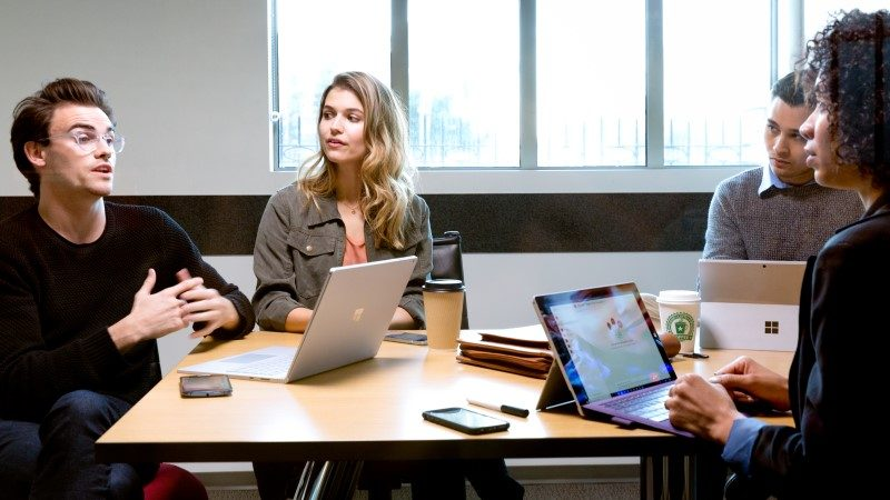 Two female and two male collegues collaborate in an office