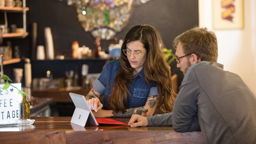 A cafe owner talks to an employee with a Surface device
