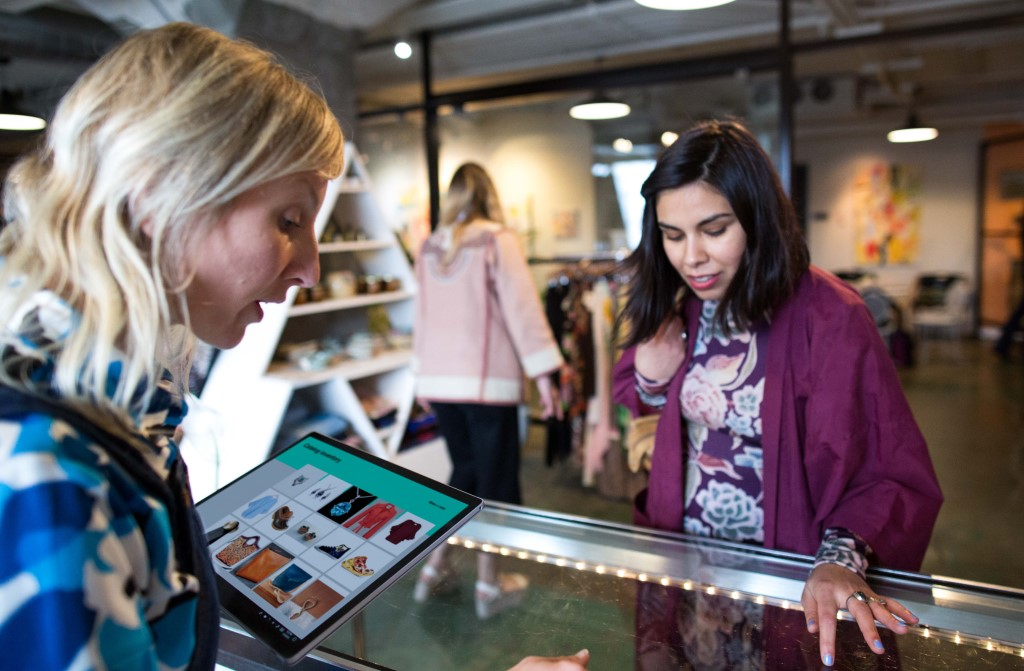 A women uses a Surface tablet and AI to help a female customer in a small SMB boutique retail shop.