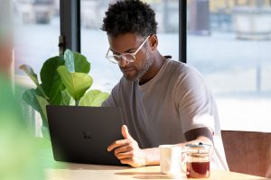 A man working remotely in a cafe using a Surface device