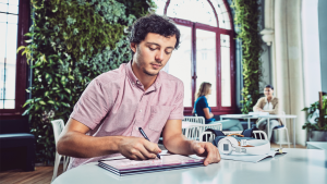 Man working on tablet in cafe