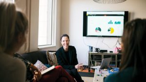 A businesswoman sits in front of a Dynamics chart and talking to two other businesswomen