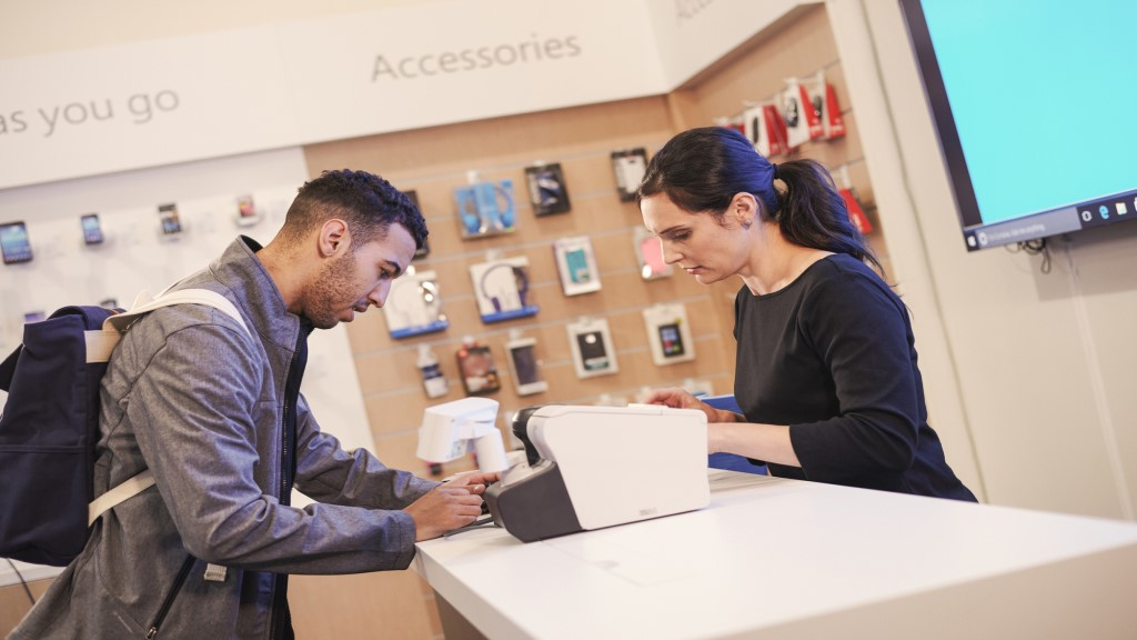 A frontline retail mobile phone employee helping a customer