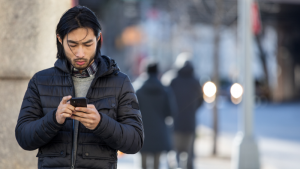 Man on street looking at his mobile phone