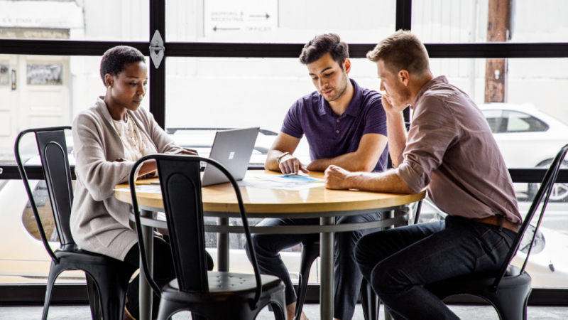 One female and two male workers sitting at round table in casual office setting or café. The woman is using a Surface Laptop, and the two men are in discussion reviewing some paperwork.