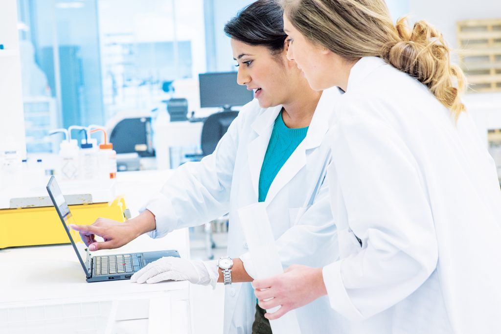 Two female doctors look at a laptop in a healthcare setting