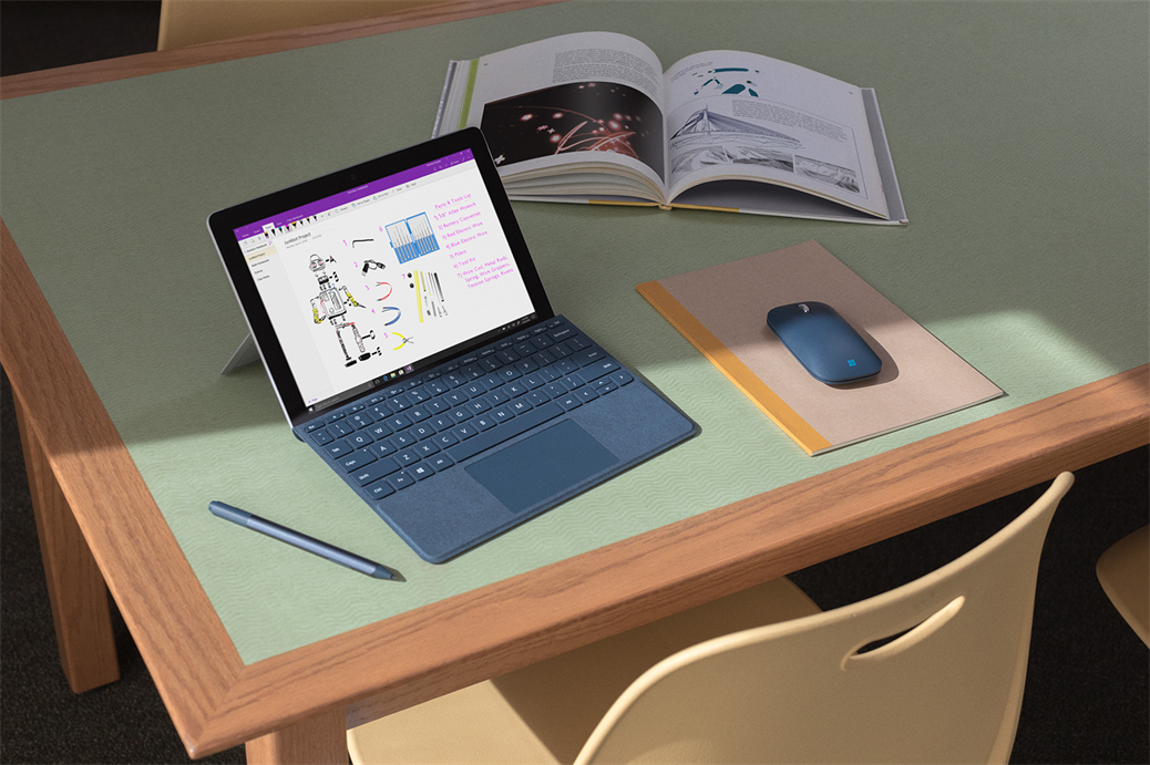 Surface Go on desk in classroom with OneNote screen. Surface Pen and Mobile Mouse.