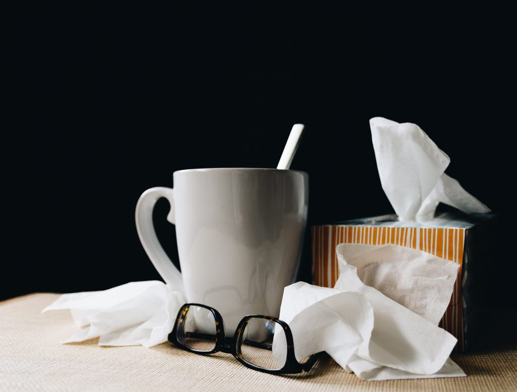 White ceramic mug on a white table beside black eyeglasses and tissues