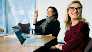 Female office worker with glasses sitting at conference room table, looking over shoulder and smiling. An open Surface Book sits on the table in front of her (screen partially visible but blurry). A female coworker sits behind her, in midst of conversation.