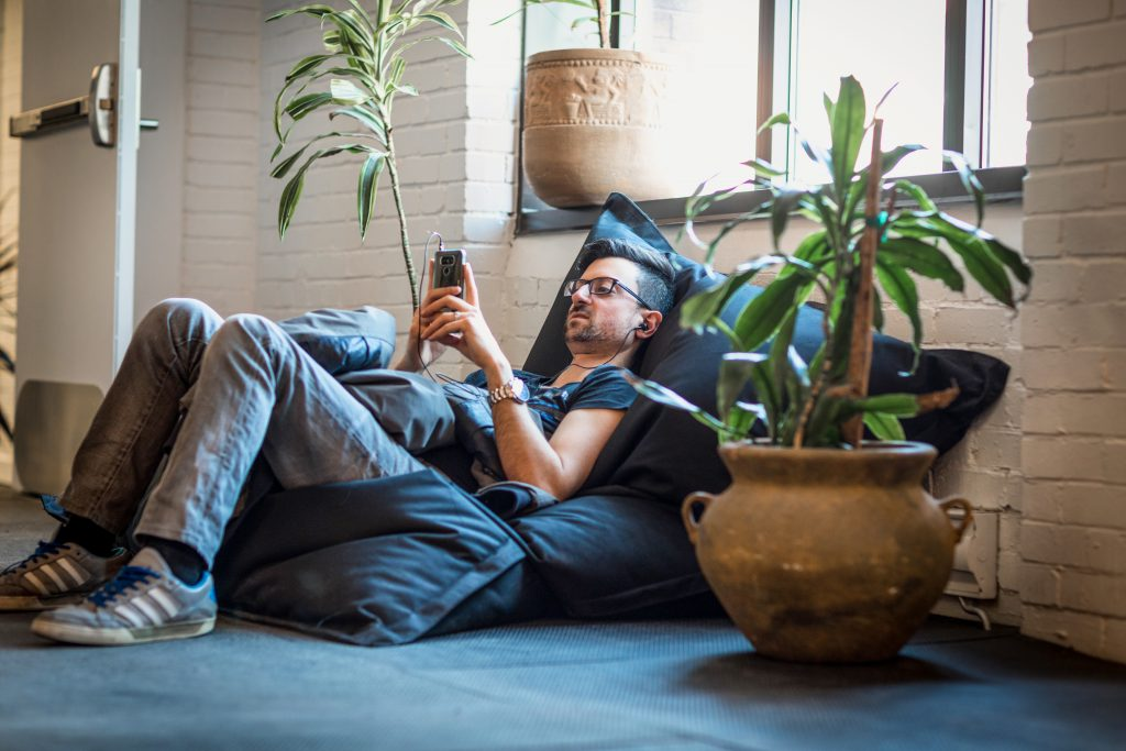 Man sitting in bean bag looking at phone in lounge area. He is leaning against wall, under a window and next to a potted plant. He is leaning against wall, under a window and next to a potted plant.