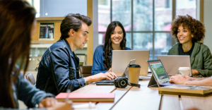 Male and female college students collaborating in group study session in library. Two Surface Pros and two laptops are on table (one Surface Pro screen shows PowerPoint slide; no other screens shown).