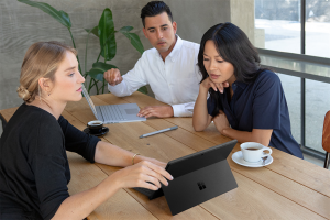 Image of a group collaborating whilst working on a Black Surface Pro 6