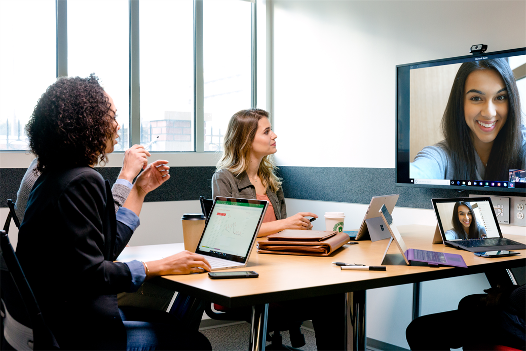 Students meeting in a conference room on a video call with their female team member