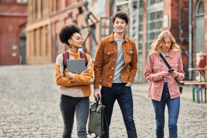 Two female and one male student on the go walking outdoors