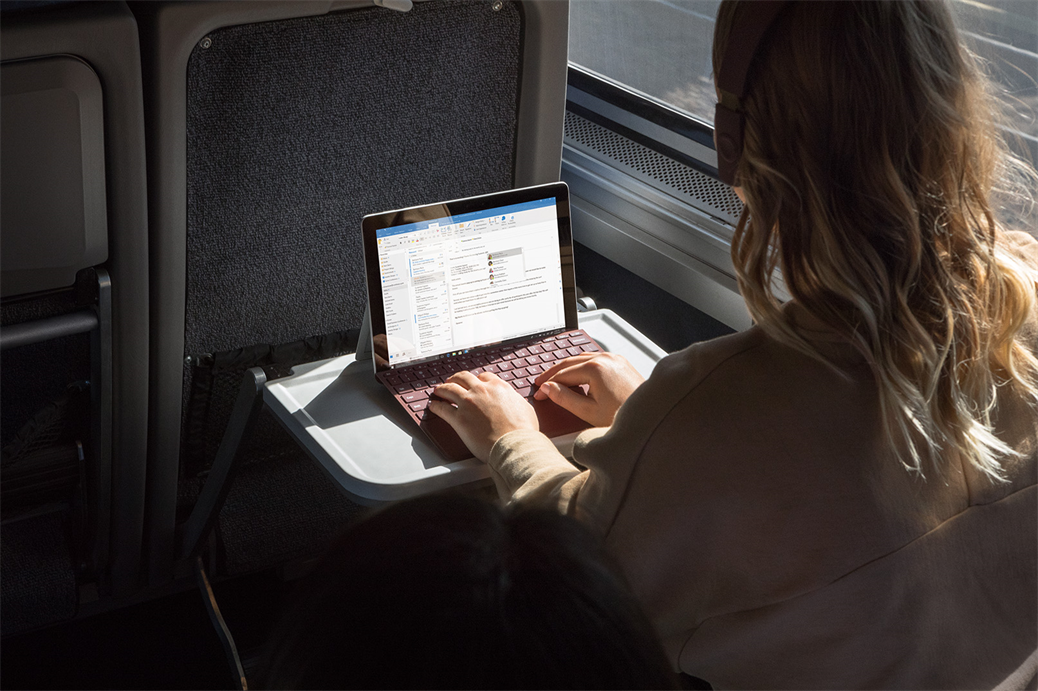 Young woman using Surface Go on the train