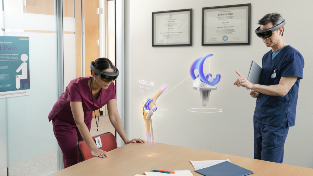 Two medical professionals exploring knee replacement hologram with Microsoft HoloLens for the purpose of surgery