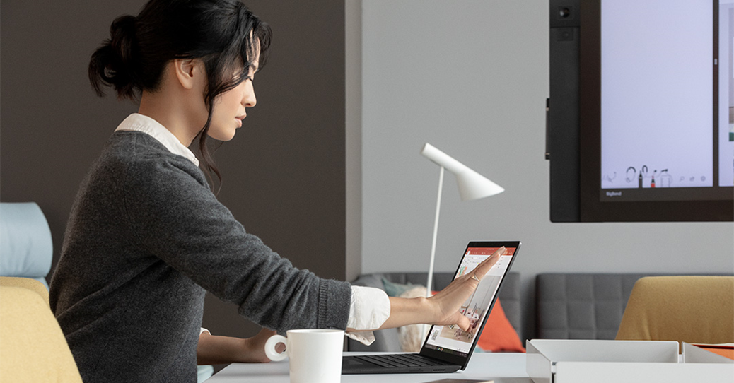 Contextual image of woman touching screen while working on Black Surface Laptop 2 inside at desk