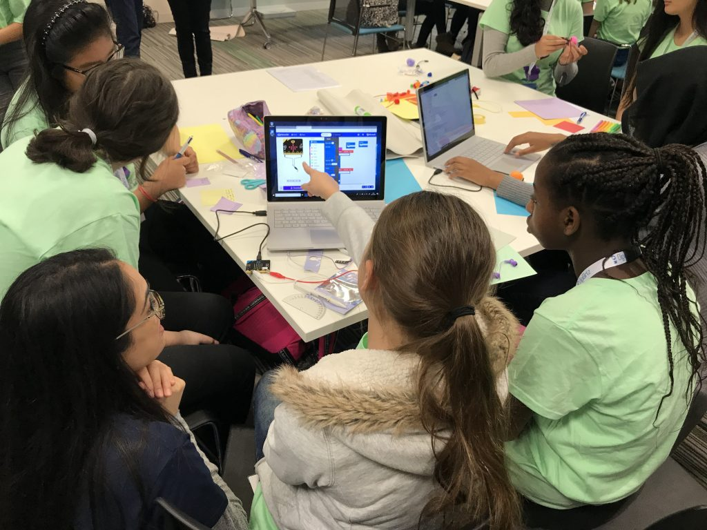 A group of young girls taking part in a Microsoft DigiGirlz event at Microsoft UK. They are all sat at a table looking at content on a Surface