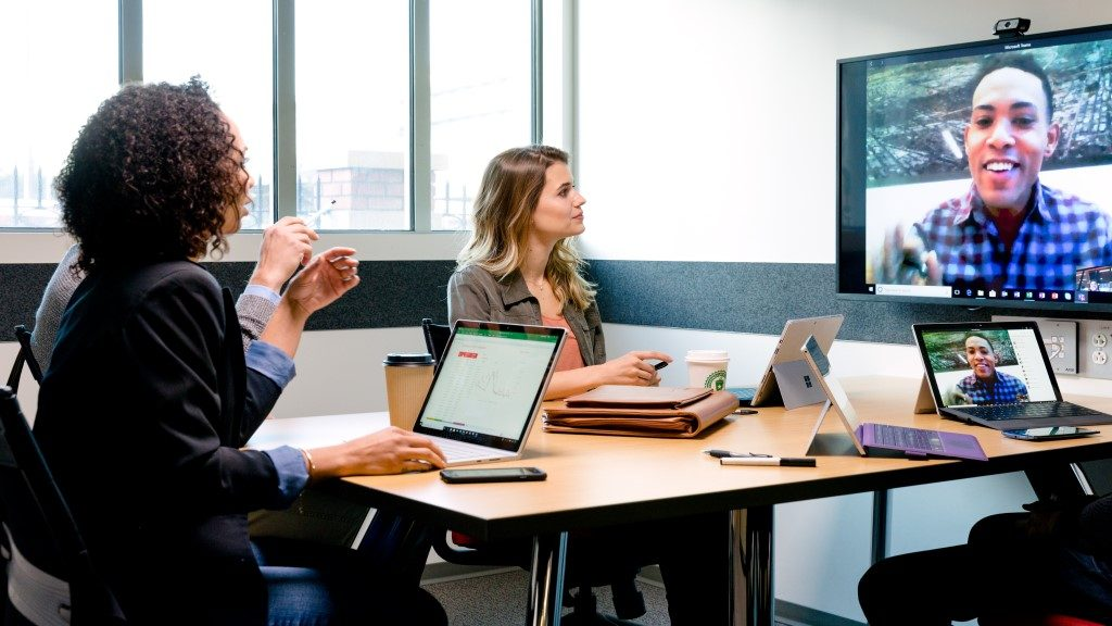 Male and female college students meeting in conference room. They are on a Skype call with another male team member, with video streaming on mounted wall monitor. Three Surface Pros and a laptop sit on table.