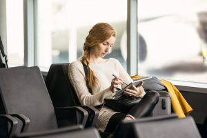 Enterprise young female achieving in airport during business travel and mobility. Including Surface Pen.
