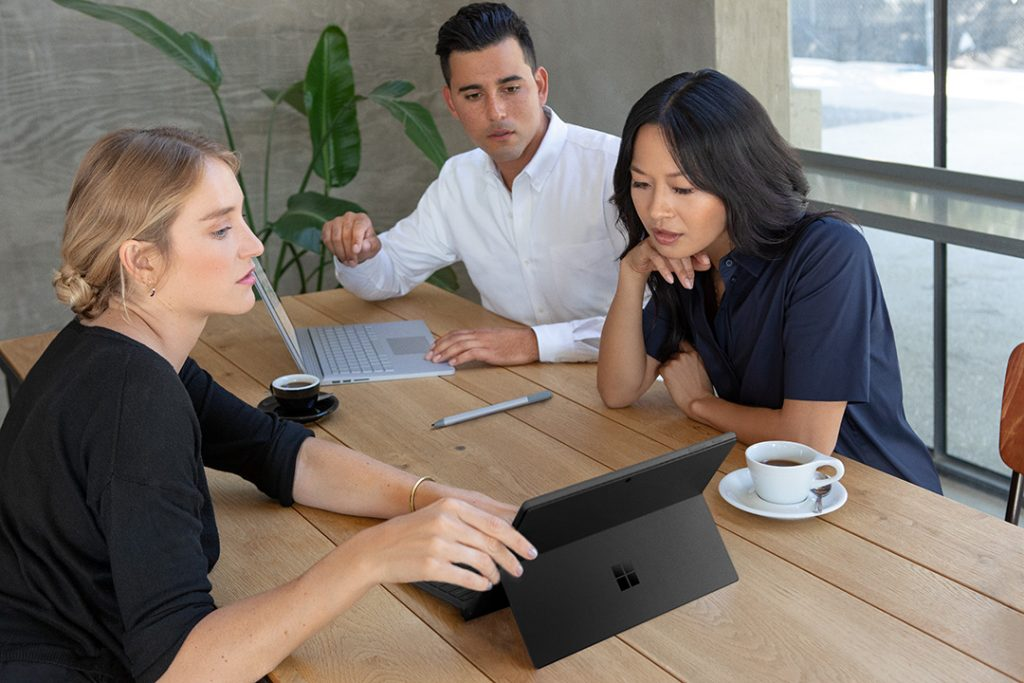 Image of group collaborating while working on Black Surface Pro 6 inside office