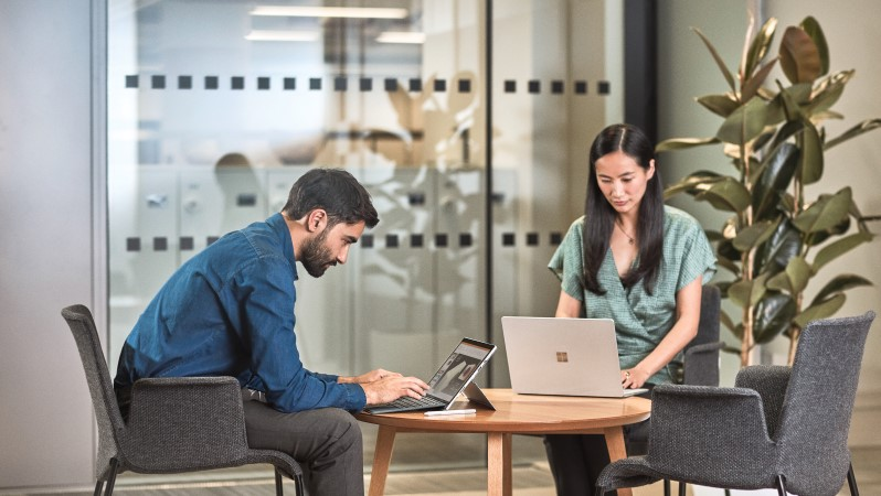 Man and woman interacting with a Surface Pro laptop.