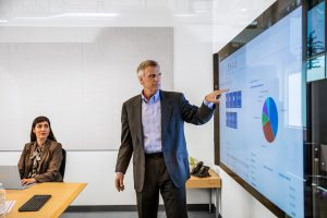 Male businessman in suit giving presentation in office conference room. He is pointing at a large monitor screen, which displays Dynamics 365