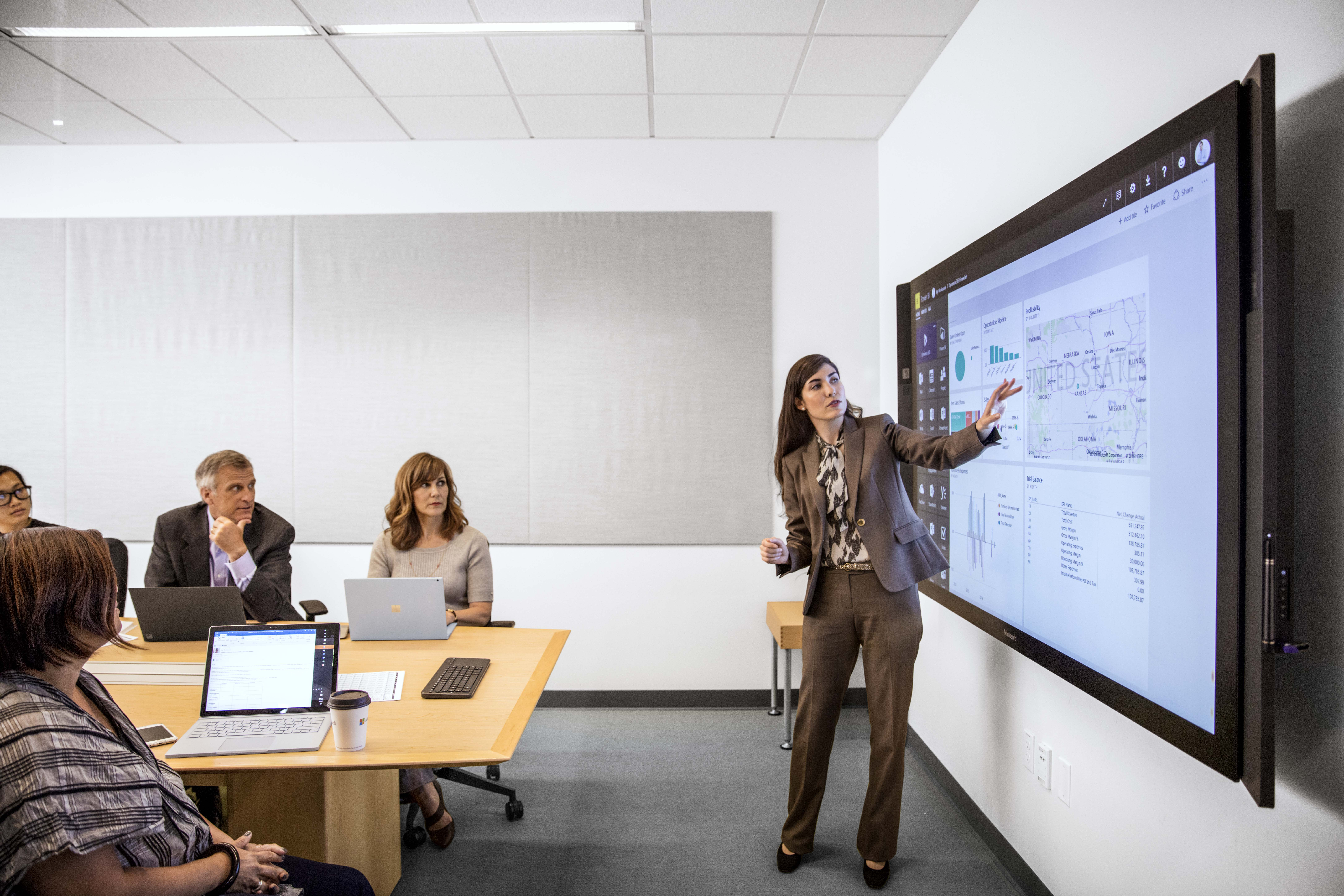 Female businesswoman in suit giving presentation in office conference room. She is pointing at a large monitor screen, which displays a map of the United States, pie charts, and graphs.