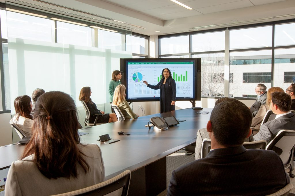 Microsoft Commercial photography. CEO leading a financial meeting using the Surface Hub.