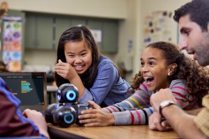 Two female students in a group including their teacher, using a Wonder Workshop Cue robot.