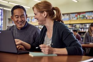 A female teacher instructing a male teacher, in a library.
