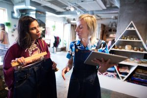 A female boutique retail store owner uses a surface tablet to check jeans inventory for a female customer.