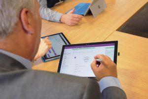 Close up of Jon and a co-worker in a meeting on Surface devices with OneNote