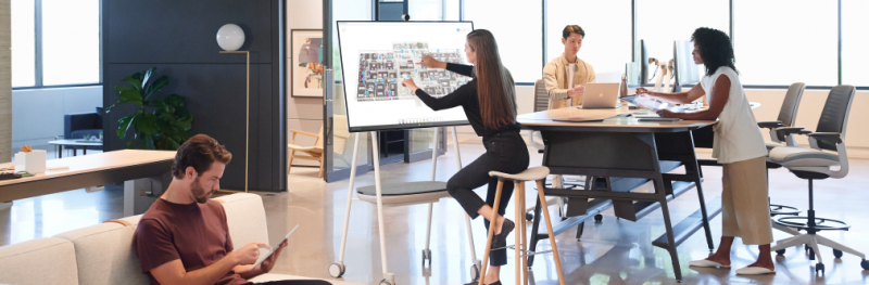 Group in office using Surface Hub 2S while on cart with battery pack using Whiteboard, Surface Pro 6, Surface Studio and Surface Book 2.