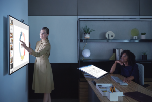 Two women executives collaborate on Surface Hub 2S in PowerPoint. Also featured Surface Studio and Outlook.