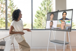 Woman executive uses Surface Hub 2S on cart with battery pack to make a Teams call.