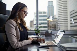 Female business executive on laptop at desk.