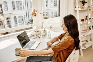 A woman is drinking coffee while using her Lenovo Yoga while sitting at her desk in her bright sun-filled apartment.