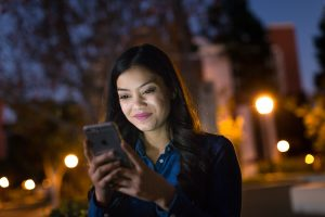 Female college student on campus at night, using phone.
