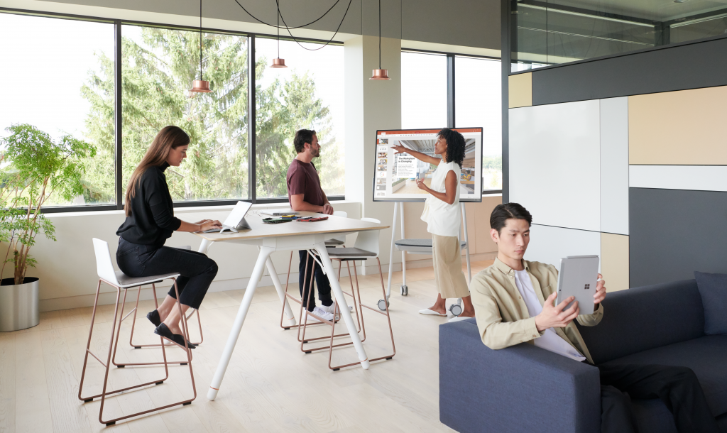 Group in open workspace using Surface Hub 2S while on cart with battery using Whiteboard, Surface Pro 6 and Surface Go.