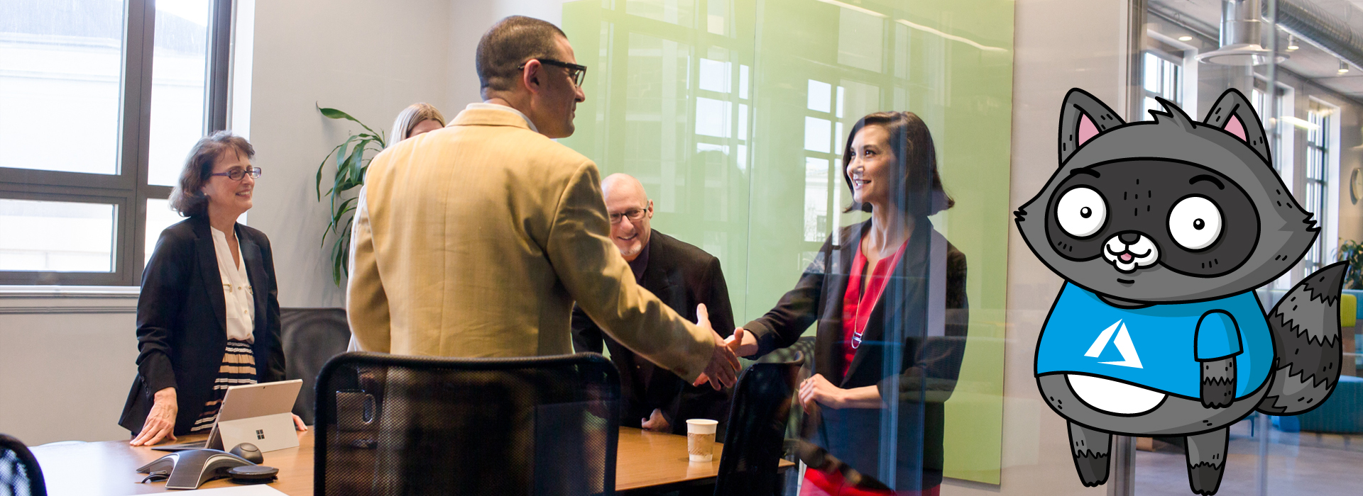 A woman and a man shaking hands in a conference room, with a picture of Bit the Raccoon on the right of the image.