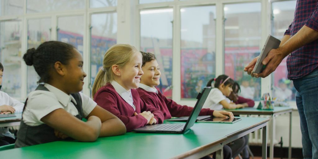 Students in front of laptops in a classroom.