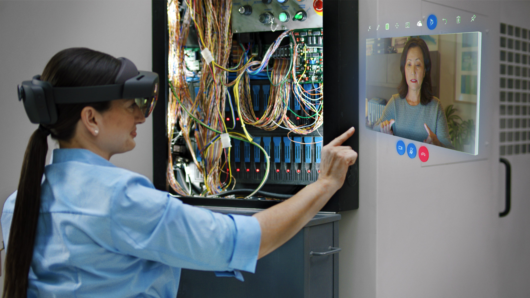 Woman interacing with Remote Assist hologram in a wiring project.
