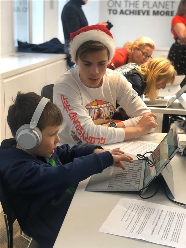 Child wearing Surface headphones and using a Surface with the help of a Microsoft employee