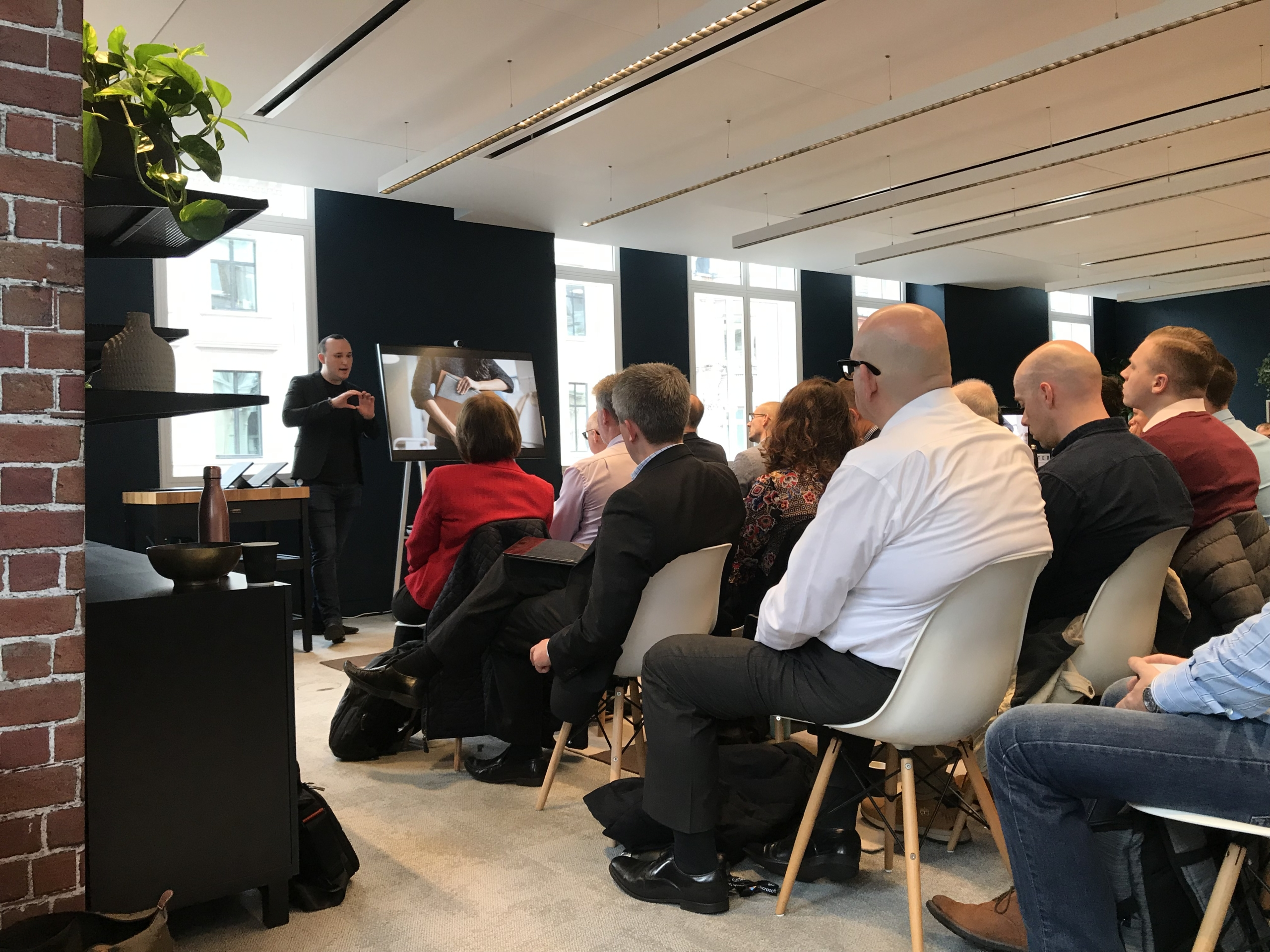 Group of customers listening to a presentation for the Surface launch event at the Microsoft Store