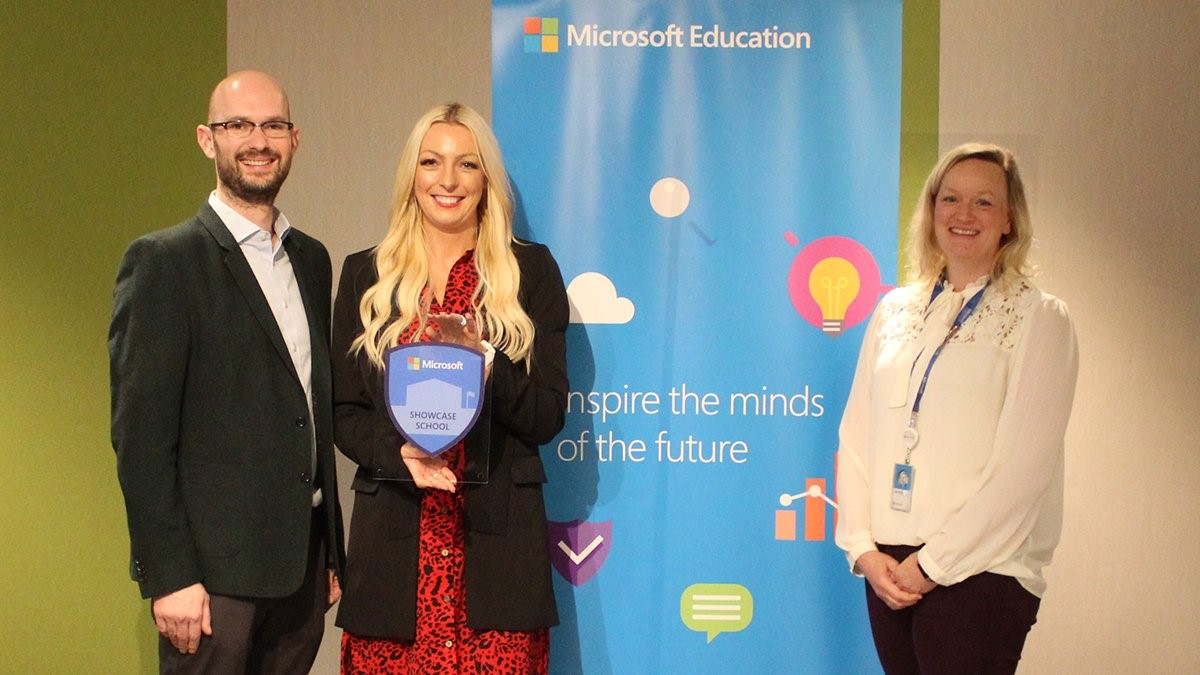 Two women and one man smiling in front of a Microsoft Education banner